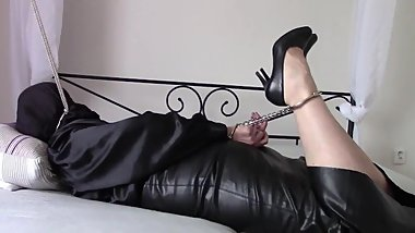 With handcuffs and hood in a long leather skirt